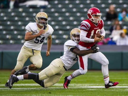 Cathedral's Kendall Coleman (doing the tackling) will play at Syracuse.