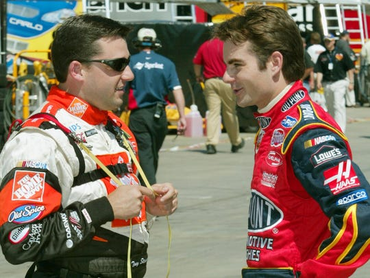 FILE – Tony Stewart left talks with Jeff Gordon right in the garage area May 23, 2002 during practice for NASCAR Coca-Cola 600 race.