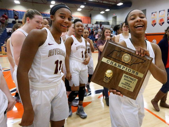 Riverdale's Anastasia Hayes (3) carries the Riverdale district championship trophy off the court after the win over  Stewarts Creek on Monday, Feb. 20, 2017, in the 7-AAA Tournament championship game.