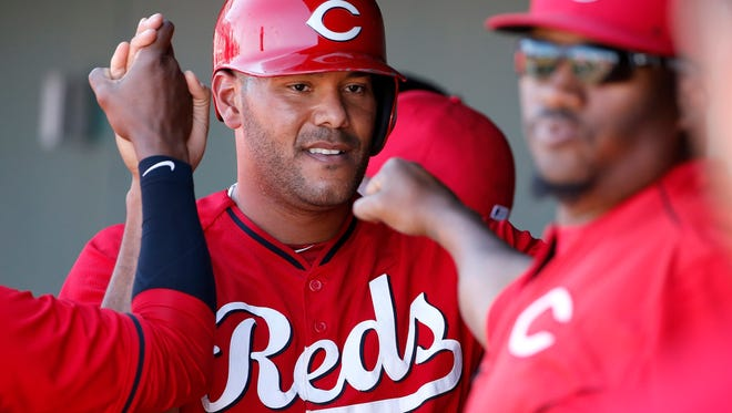 Cincinnati Reds' Chris Dominguez smiles as he is congratulated in the dugout by teammates after scoring a run against the Cleveland Indians during the fourth inning of a spring training baseball game Thursday, March 26, 2015, in Goodyear, Ariz.  The Reds defeated the Indians 13-2.