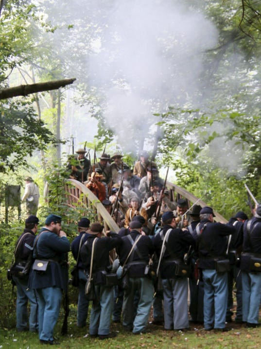 Kerri Fleegle - For Public Opinion   Re-enactors skirmish at a bridge Saturday, Aug. 8, 2015, in Renfrew Park, Waynesboro, during the 35th Civil War Soldiers Encampment.  Activities included dress parades, firing competition, unscripted battles,  a period baseball game and church services.