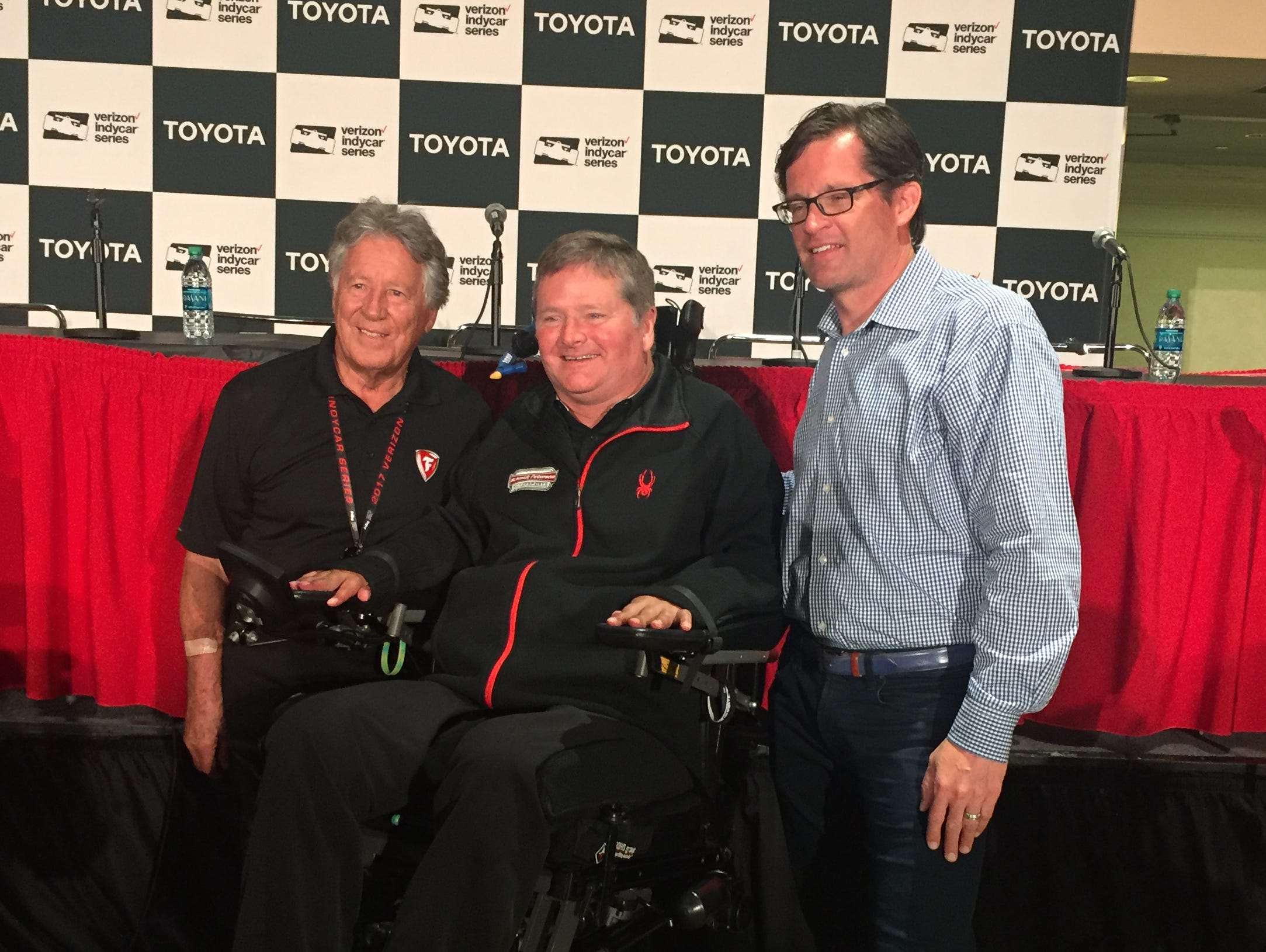 Racing legend Mario Andretti, team owner Sam Schmidt and Indianapolis Motor Speedway president Doug Boles pose for a photo after their news conference announcing a race between Andretti and Schmidt in semi-autonomous cars at IMS.