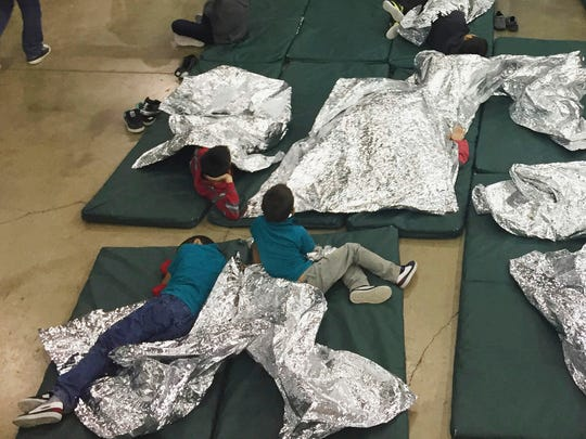 In this photo provided by U.S. Customs and Border Protection, people who've been taken into custody related to cases of illegal entry into the United States, rest in one of the cages at a facility in McAllen, Texas, Sunday.