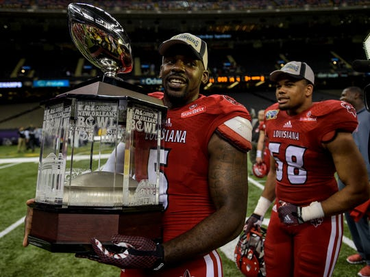 UL Ragin' Cajuns quarterback Jalen Nixon (5) carries the  the R+L Carriers New Orleans Bowl championship trophy on the field after the team's 16-3 victory over the Nevada Wolf Pack at the Mercedes-Benz Superdome in New Orleans, La., Saturday, Dec. 20, 2014.