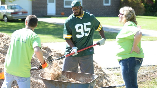 Green Bay Packers defensive end Datone Jones, center, helps to shovel mulch with Humana Cares volunteers while building a playground at Sand Hill Park.