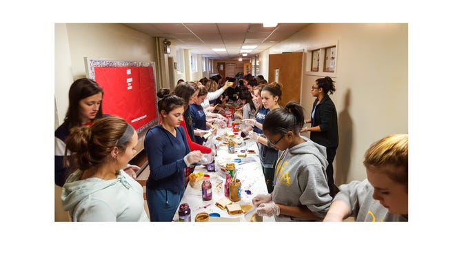 As part of Our Lady of Mercy Academy's Catholic Schools Week activities, students spent a lunch period making 100s of peanut butter and jelly sandwiches for people in need.