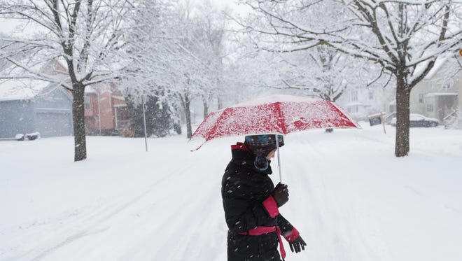 Dandan Guo walks through the snow along E. Second Street in Flint on Wednesday, February 24, 2016.