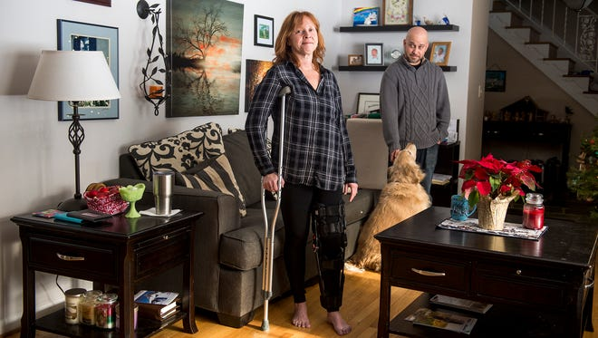 Stephanie Navratil stands for a portrait in her Spring Garden Township living room as husband John Navratil and golden retriever Nala look on Wednesday, Jan. 3, 2018. At age 23, Stephanie Navratil was trapped in her car for four hours after crashing on her way home from work early New Year's Day in 1998. Suffering injuries to her jaw, pelvis and legs, Navratil underwent multiple surgeries and extensive therapy that have enabled her to pursue a full life with her family and three children. Navratil is currently using a leg brace and a crutch after undergoing knee surgery in November.