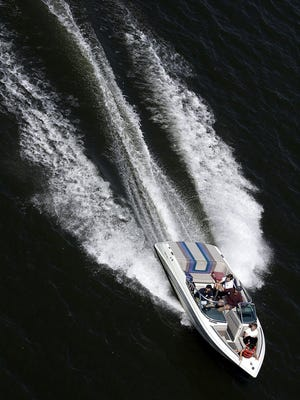 A power boat cuts a swath through the Willamette River in downtown Portland.