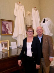 """Debbie and Mark Crocker stand in front of the display featuring her wedding dress at the """"Wedding Dresses Through the Decades"""" exhibit at Oaklands Mansion."""