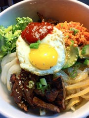 The bibimbap is a combination of sautéed carrots, onions, zucchini, mushrooms, marinated steak, Korean radish, fresh lettuce and a fried egg over rice with Gochujang sauce.