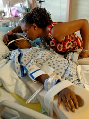 Elaine Bias kisses her daughter in the intensive care
