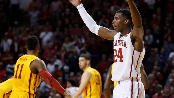 Oklahoma guard Buddy Hield (24) gestures to the crowd in the first half of an NCAA college basketball game against Iowa State in Norman, Okla., Monday, Feb. 9, 2015.