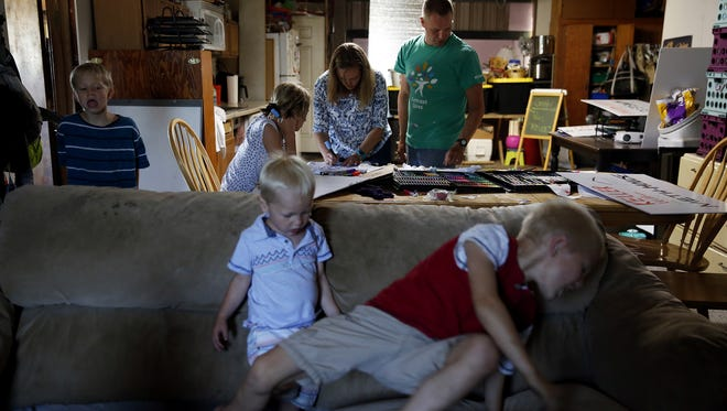 Seven-year-old Talon Tubbs (left), Trevan, 2, and Teancum, 6, play around a living room couch as Tathena, 11, helps her parents Denay and Travis create shirts and posters for a protest while inside a converted garage on the Tubbs' property in Jefferson, Oregon, on Wednesday, Aug. 1, 2018.