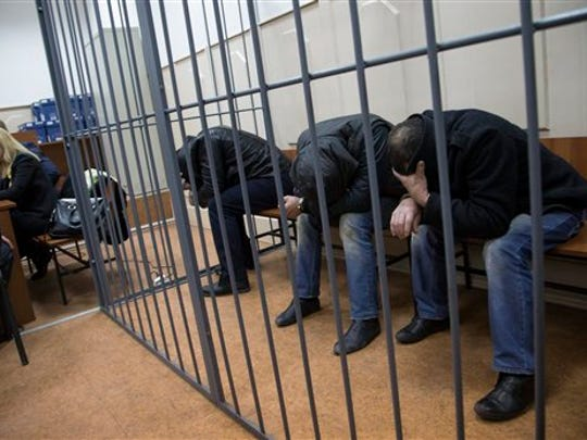 Three men suspected of involvement in the killing of Boris Nemtsov sit in a court room in Moscow, Russia, on  Sunday, March 8, 2015. A Russian court on Sunday charged two men in the killing.