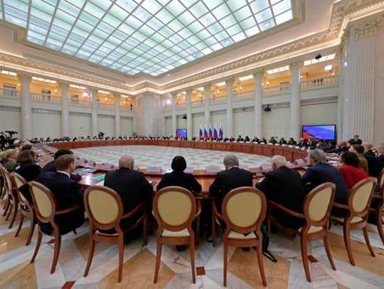 Russian President Vladimir Putin, center right at rear,
