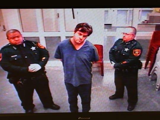 Murder suspect John Jonchuck Jr., center, appears via