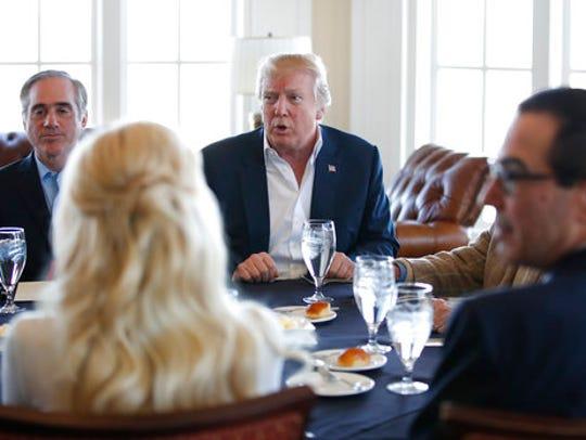 President Donald Trump, center, meets Treasury Secretary