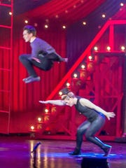 "Noah Grimm leaps over Julianne Roberts during the Brighton High School musical ""Pippin."""