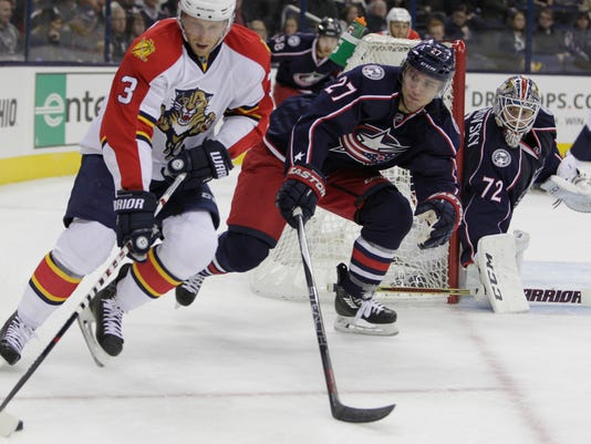 Florida Panthers' Steven Kampfer, left, looks for an open pass as Columbus Blue Jackets' Ryan Murray, defends and Blue Jackets' Sergei Bobrovsky, of Russia, protects the net during the first period of an NHL hockey game Friday, Dec. 4, 2015, in Columbus, Ohio. (AP Photo/Jay LaPrete)