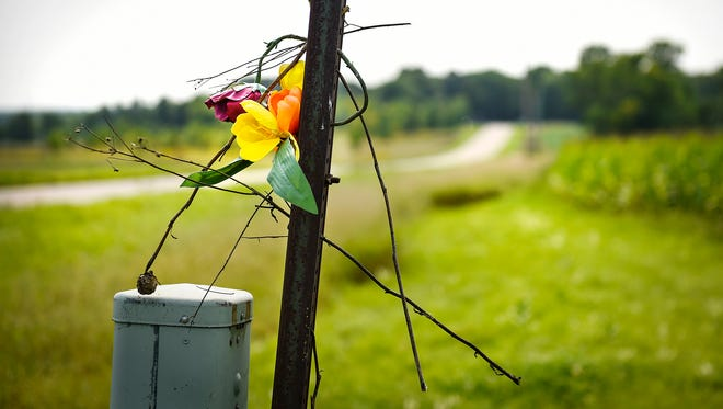 A few flowers hang on a post in St. Joseph Thursday, Aug. 31, near the area where Jacob Wetterling was abducted in 1989.