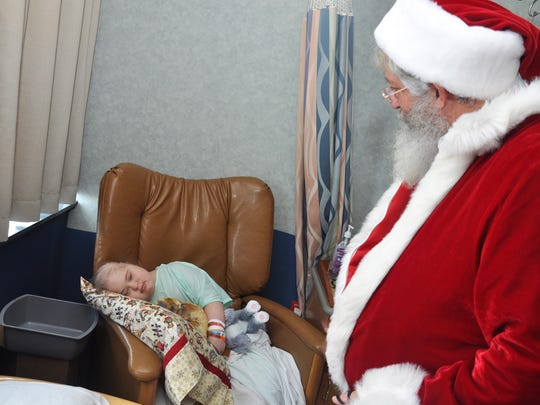 Rebecca Perdue, 11, smiles at a personal greeting from Santa (Dan Sutter), who gave her a teddy bear on Christmas morning at Golisano Children's Hospital.