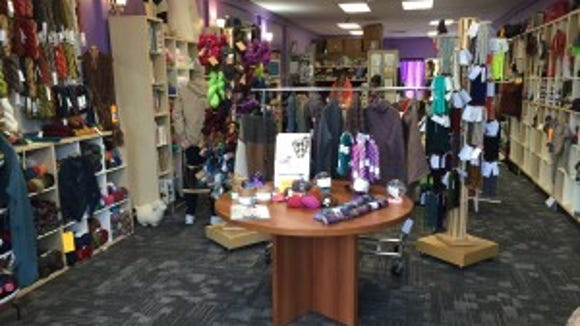 Special yarns and books are featured on this table in the front of the store.