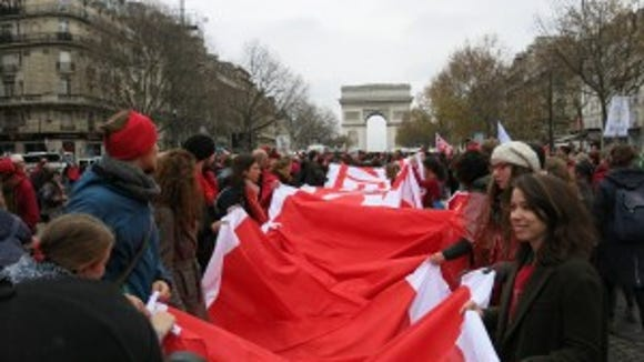 Red line for climate justice unfurled at Arc de Triomphe.