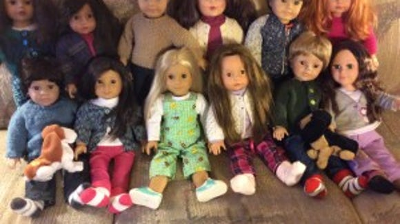 My family of 12 dolls and growing is taking up most of the space on my couch, but they're a lot of fun to have around. See how many of them are wearing sweaters I've made?
