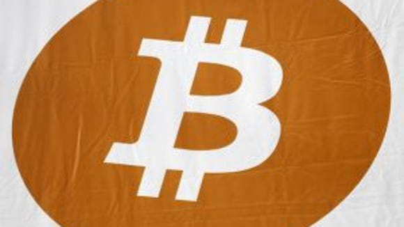 A bitcoin logo is displayed at the Inside Bitcoins conference and trade show, April 7, 2014, in New York. (Photo: Mark Lennihan, AP)