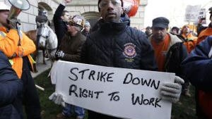 Jake Kincaid carries a sign as he protests during a 2012 rally at the State Capitol in Lansing, Mich., against right-to-work legislation.