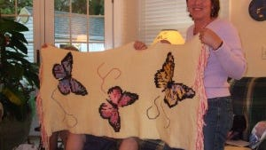 Val Yacik (standing) and a member of the prayer shawl group from Dayton holding a butterfly shawl from the Dayton group.