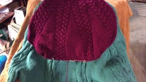 Here is the new poncho laid on top of the old one. It  looks narrower than it actually is because it's on a 40-inch circular needle.