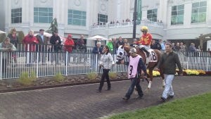 Turkish riding star Halis Karatas at Churchill Downs Saturday, with trainer Murat Sancal, also of Turkey, walking alongside his horse.