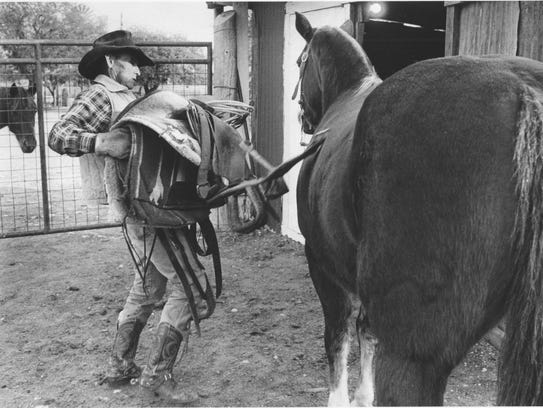 Gene Crisp pulls the saddle off his horse after a day's