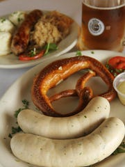 Foreground, veal weisswurst is served with a soft pretzel