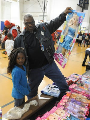 Leroy Gill a member of the Thunderguard Motorcycle Club poses for a photo with Curniah Gregory, 6, of New Castle with her toy at their annual toys for kids party with food and games at the Police Athletic League of Wilmington.
