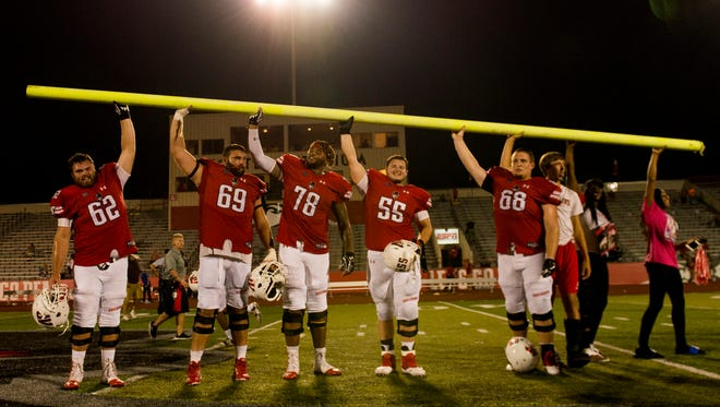 Austin Peay players stand in the middle of the field, holding part of a goal post they tore down after winning their game against Morehead State.