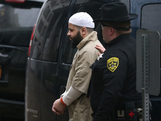 Mufid Elfgeeh is led into the Federal Building under