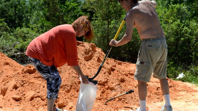 Scott Carlson helps Dee Watt fill sand bags at Tiger Point Park on Thursday in preparation for possibly more flooding since more rain is in this wekend's forecast.