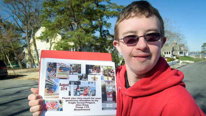 Alexander King, 19, of Beachwood, helped create new dog waste stations in Pine Beach for his Eagle Scout project, including this one at the intersection of Riverside Drive and New Jersey Avenue. Here, he is pictured with his a scrap book that shows the work that was done to build the station. Photo was taken on Wednesday, March 30, 2016.