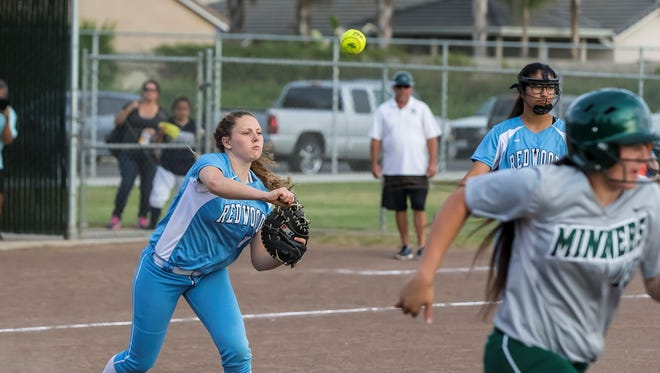 Redwood's Mackenzie Darnell, left, attempts to throw out El Diamante's Janelle Tumacder at first base on Tuesday during a West Yosemite League softball game.