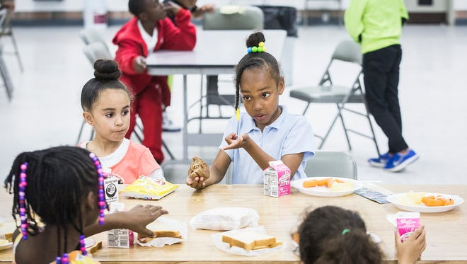"""Children have an after school meal on """"Donut Friday"""" at the Unity Center Friday afternoon."""