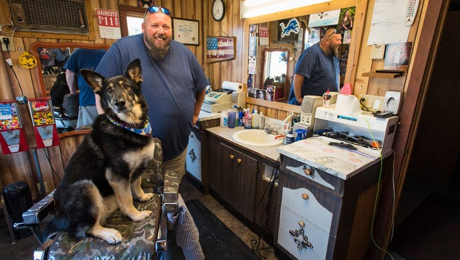 Jason Milhoan and his 7-year-old German Shepard, Isabella, stand inside the Lakeport Barber Shop Tuesday, May 8, 2018. Milhoan bought the barber shop from his brother eight years ago.