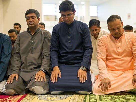 People pray during an Eid al-Fitr celebration, marking