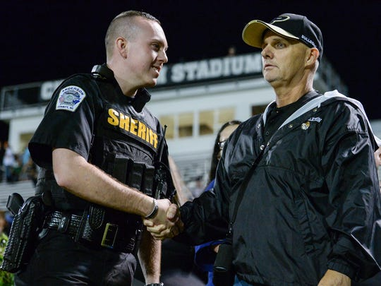 David Elgin, left, an Anderson County Sheriff Deputy, shakes hands with Paul Sutherland after he was honored at halftime of the game with Crescent at Pendleton on Friday. Elgin was one of the men and women who helped him the night he had his heart attack after the game with Powdersville.