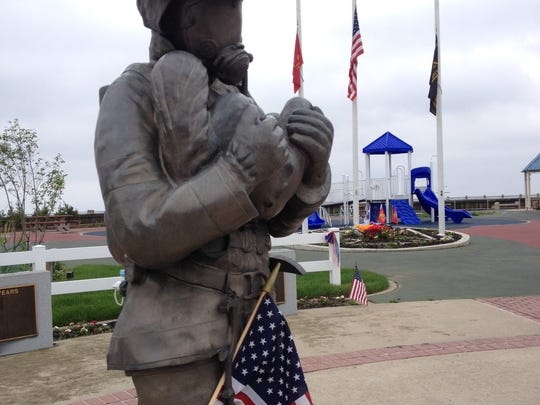 """Flags at half staff at firemen's park today in Union Beach, where statue honors fallen firefighter Gustave Dirner, Jr., """"who made the ultimate sacrifice by giving his life serving his community"""" on Oct. 11, 1987, according to the inscription."""