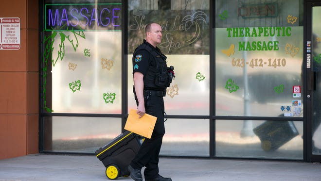 A Glendale police officer carries evidence from the  Shanghai La Spa, a massage parlor, on the 6600 block of West Cactus Road in Glendale on Wednesday, Oct. 21, 2015.