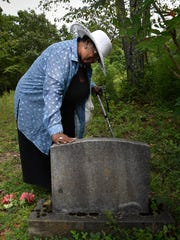 Helen Joyce Vance touches the headstone of a relative