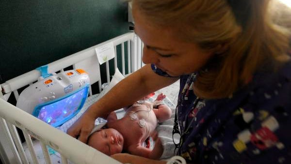 Nurse Cathy Hocutt dresses 2-week-old Urijah at East Tennessee Children's Hospital in Knoxville in May 2014. Urijah was born dependent on drugs.